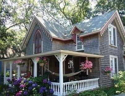 pretty shingled house with flowers outside